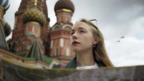 Сконцентрированный молодой турист смотря карту стоя около Кремля, лета России акции видеоматериалы