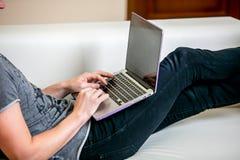 Сконцентрированный молодой человек с деятельностью стекел на компьтер-книжке в домашнем офисе Печати на клавиатуре и переченях от стоковое изображение rf