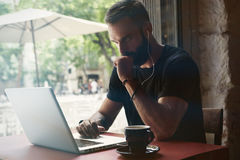 Сконцентрированный молодой бородатый бизнесмен нося кафе компьтер-книжки черной футболки работая городское Кофе чашки таблицы чел Стоковое Изображение RF