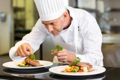 Сконцентрированный мужской шеф-повар гарнируя еду в кухне