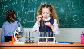 Сконцентрированный на изучать Микроскоп химии студенты делая эксперименты по биологии с микроскопом Маленькие ребята уча стоковое изображение rf