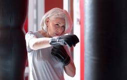 Сконцентрированный довольно серый с волосами бокс женщины в спортзале Стоковые Изображения