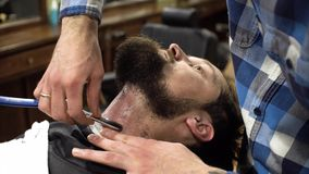 Сконцентрированный парикмахер брея бороду клиента с бритвой парикмахера акции видеоматериалы