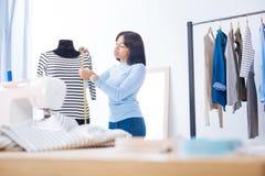 Сконцентрированный портной измеряя длину блузки пока находящся на работе стоковые фото