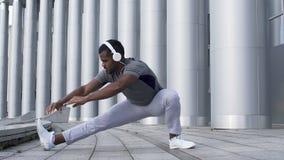 Сконцентрированный спортсмен делая боковой выпад для того чтобы подготовить мышцы подколенного сухожилия видеоматериал