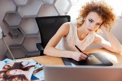 Сконцентрированный фотограф женщины обрабатывая изображения используя графическую таблетку в офисе Стоковое Изображение
