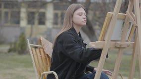 Сконцентрированный художник женщины сидя перед деревянным мольбертом рисуя изображение Красивый человек приходит и покрывает глаз акции видеоматериалы