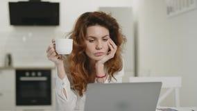Сконцентрированный чай женщины выпивая на кухне утра Ноутбук молодой дамы работая видеоматериал