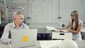 Сконцентрированный человек и молодая женщина работая в офисе видеоматериал