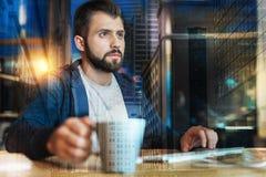 Сконцентрированный человек работая в его офисе пока выпивающ чай Стоковое фото RF