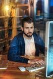 Сконцентрированный человек смотря монитор пока работающ в его офисе Стоковое Фото