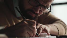 Сконцентрированный человек с бородой, работами стекел с чертежами, делает примечания видеоматериал