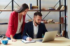 Сконцентрированный человек и женщина смотря компьтер-книжку Стоковые Фото