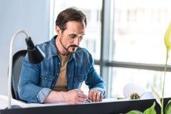 Сконцентрированный человек создавая проект в офисе Стоковые Изображения