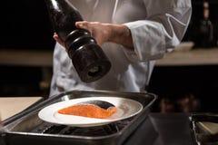 Сконцентрированный шеф-повар кладя соль на salmon стейк Стоковое Изображение