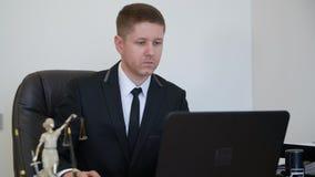 Сконцентрированный юрист работая на его ноутбуке на его таблице работы видеоматериал