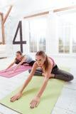 : 2 сконцентрированных девушки делая протягивающ тренировки Стоковое фото RF