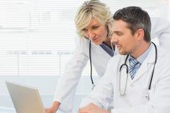 2 сконцентрированных доктора используя компьтер-книжку совместно Стоковые Изображения