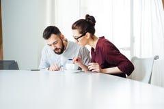2 сконцентрированных предпринимателя работая совместно в офисе Стоковая Фотография RF
