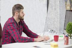 Сконцентрировано на работе Сконцентрированный молодой человек бороды работая на компьтер-книжке пока сидящ на его месте службы в  стоковые фото
