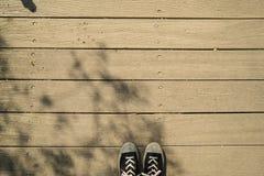 Скопируйте космос для образа жизни путешествием тапок с черно-белыми ботинками, деревянным полом зерна прокладок планки и предпос Стоковое Изображение