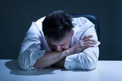 Скорбный человек сидя на таблице Стоковая Фотография RF