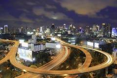 Скоростное шоссе в ноче с автомобилями освещает в современном городе стоковое фото rf