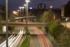 Скоростное шоссе с городским движением ночи с фокусировать на дороге Автомобиль стоковое фото rf