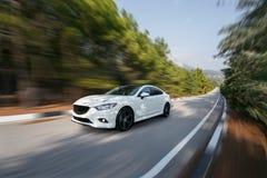 Скорость белого автомобиля быстрая управляя на дороге асфальта на дневном времени стоковые изображения rf