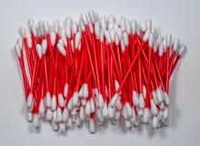 Скольжение пробирок хлопка сложенное Красные пластичные ручки славно сравнивают на светлой предпосылке Стоковые Изображения