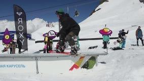 Скольжение Snowboarder на железном следе лыжа курорта смелости день солнечный весьма спорт акции видеоматериалы