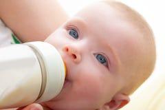 Скрепленные маленькие голубые глазы младенца выпивая молоко бутылки стоковое фото