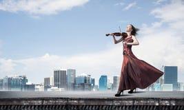 Скрипач женщины в красном платье играя мелодию против облачного неба Мультимедиа стоковые фотографии rf