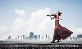 Скрипач женщины в красном платье играя мелодию против облачного неба Мультимедиа стоковая фотография rf