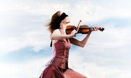 Скрипач женщины в красном платье играя мелодию против облачного неба стоковое фото