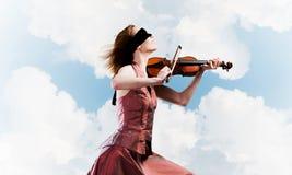 Скрипач женщины в красном платье играя мелодию против облачного неба стоковое изображение rf