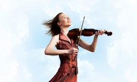 Скрипач женщины в красном платье играя мелодию против облачного неба стоковые изображения