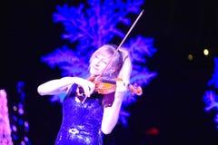 Скрипач женщины играя музыку праздника на шоу рождества в международной зоне привода стоковое фото rf