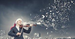 Скрипка игры женщины Санты Стоковые Фото