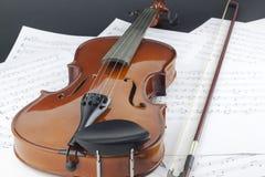 Скрипка и смычок на музыкальных примечаниях стоковое фото rf