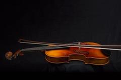 Скрипка и смычок на черной предпосылке с зоной экземпляра Стоковое Фото