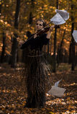 Скрипка скрипки молодой женщины над бумагой музыки летания и падение паркуют предпосылку Стоковые Фотографии RF
