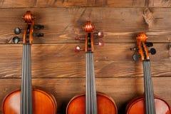 Скрипки в деревянной предпосылке Стоковая Фотография RF
