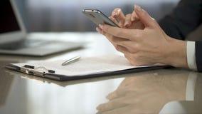 Скроллинг дамы и печатать на экране мобильного телефона, нового назначения календаря сток-видео