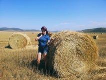 Скромная девушка страны представляя около связки сена Стоковые Изображения