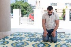 Скромная мусульманская молитва человека в мечети стоковое фото rf