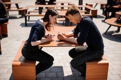 Скрытные пары с умными телефонами в их руках - молодой взрослый имеет технологию проблем уединения современную Стоковые Изображения RF