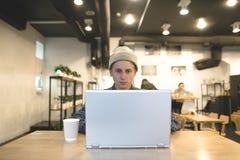 Скрытые битники сидят на таблице в уютном кафе и работают на компьютере Фрилансер с компьтер-книжкой работает в кафе Стоковые Изображения