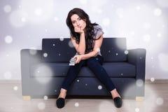 Скука зимы - детеныши пробурили женщину сидя на софе и наблюдать Стоковая Фотография RF
