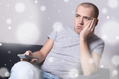 Скука зимы - пробуренный человек сидя на софе и смотря кино или Стоковая Фотография